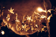 Golden shining stars with sparkling Christmas lights in golden colors in Christmas night as Christmas background Stock Photos