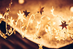 Golden shining stars with sparkling Christmas lights in golden colors in Christmas night as luxury Christmas background stock images