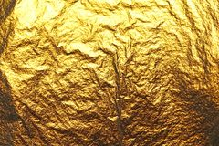 Golden shiny background. Bright golden background, sparkles and. Shines. A brush stroke.Foil Stock Images
