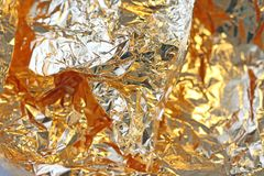 Golden shiny background. Bright golden background, sparkles and. Shines. A brush stroke.Foil Stock Photos