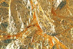 Golden shiny background. Bright golden background, sparkles and. Shines. A brush stroke.Foil Stock Photo