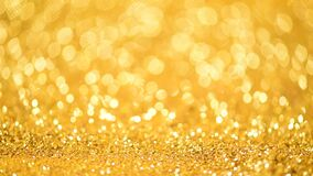 Golden shiny background for Christmas greetings. Banner with defocused lights, bright yellow bokeh. Shimmer of gold