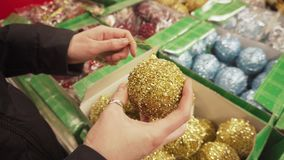 Golden shiny ball for the Christmas tree in female hands. Girl chooses new year toys. stock footage
