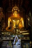 Golden shiny Buddha in a dark Temple stock photo