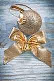 Golden shiny Christmas ball bow on wooden board holidays concept Stock Images