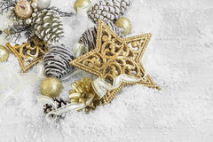 Golden Shiny Christmas Decorations in the Snow with Elegant Ribb Royalty Free Stock Images