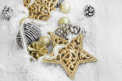 Golden Shiny Christmas Decorations in the Snow with Elegant Ribb Stock Photo