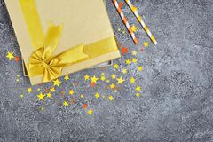 Golden shiny classic gift box with satin bow and paper cocktail straws with confetti in the shape of stars as attributes of party royalty free stock photos