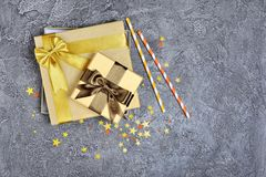Golden shiny classic gift boxes with brown satin bows and paper cocktail straws with confetti in the shape of stars as attributes royalty free stock photo