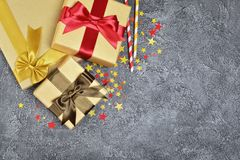 Golden shiny classic gift boxes with color satin bows and paper cocktail straws with confetti in the shape of stars as attributes royalty free stock image