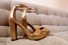 Golden shoes on a couch Stock Photo