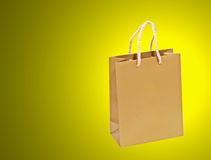 Golden shopping bag on a yellow background. Royalty Free Stock Images