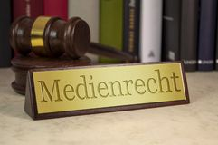 Golden sign with gavel on a desk with the german word for Media Law - Medienrecht. Golden sign with gavel on a desk with law books the german word for Media Law royalty free stock photos