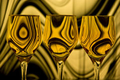 Golden Silhouette. Close up of three wine glasses; backlighting through coloured, patterned glass stock image