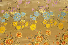 Golden silk with floral pattern Royalty Free Stock Photography
