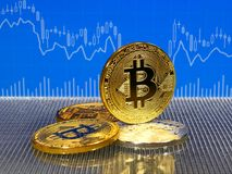 Golden and silver bitcoin coins on blue abstract finance background. Bitcoin cryptocurrency. Golden and silver bitcoin coins on blue abstract finance background Stock Image