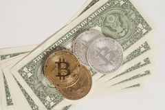 Golden and silver bitcoin coins and one dollar banknotes Royalty Free Stock Photo
