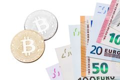 Golden and silver Bitcoins close-up Bitcoins and euros on white royalty free stock image