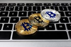 Golden and silver bitcoins on computer keyboard. Closeup stock images