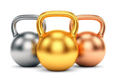 Golden, silver and bronze kettle bells Royalty Free Stock Image