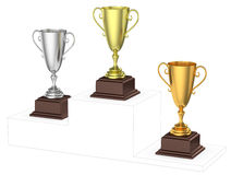Golden, silver and bronze trophy cups on imaginary winners podiu Stock Photography