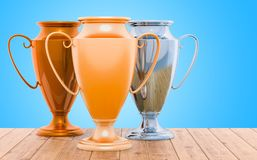 Golden, silver and bronze trophy cups on the wooden table, 3D re. Golden, silver and bronze trophy cups on the wooden table, 3D stock illustration
