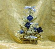 Golden and silver Christmas tree with black cards that say Happy Stock Photo