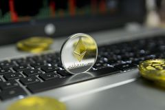 Golden Silver Ethereum coin with gold coins lying around on a black keyboard of silver laptop and diagram chart graph on royalty free stock photo
