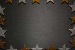 Golden, silver stars as frame on black slate background Stock Image