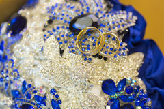 Golden and silver wedding rings on wedding bouquet of brooches. Golden and silver wedding rings on wedding bouquet of shiny dark blue brooches Royalty Free Stock Photo