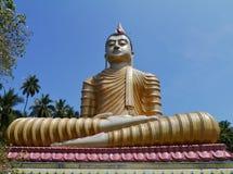 A golden sitting Buddha opposite a blue sky Stock Photo