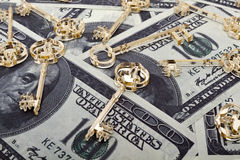 Golden keys on dollars. Golden skeleton keys made of plexiglas lie on dollars background. Horizontal orientation royalty free stock photography