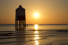 Golden skies. Sunset over the wooden lighthouse on Burnham on Sea beach in Somerset, UK Royalty Free Stock Images