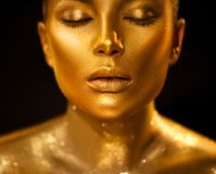 Golden skin woman face. Fashion art portrait closeup. Model girl with holiday golden glamour shiny professional makeup. Gold jewelry, accessories royalty free stock image