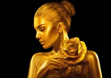 Golden skin woman with rose. Fashion art portrait. Model girl with holiday golden glamour shiny professional makeup. Gold jewellery, accessories stock images