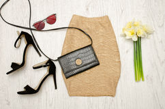 Golden skirt, shoes, clutch, glasses and a bouquet of daffodils. Fashionable concept. Wooden background Stock Images