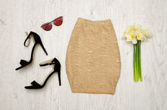 Golden skirt, shoes, glasses and a bouquet of daffodils. Fashionable concept. Wooden background Stock Photos