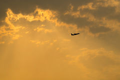 Golden sky background, sunset sky with silhouette plane Royalty Free Stock Images