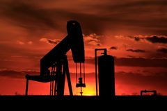 Golden Sky with Oil Well Pump Silhouettes. A Kansas Sunset with a Golden Sky with an Oil well Pump Silhouette shot south of Nickerson Kansas out in the Country Stock Photos