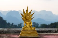 Small statue of Buddha in the Wat Tham Suea Tiger cave temple on the background of the silhouettes of the mountains in. Golden small statue of Buddha in the Wat royalty free stock photography