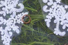 Golden smoth wedding rings on white veil of bride on green grass Royalty Free Stock Photography