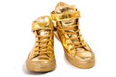 Golden sneakers Stock Photos