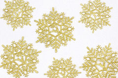 Golden snow flakes with glittering white background. Christmas t Royalty Free Stock Photography