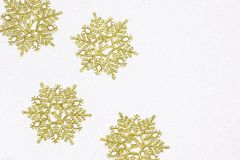Golden snow flakes with glittering white background. Christmas theme. Stock Image