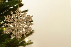 Golden snowflake ornament hanging on the Christmas tree. stock photos