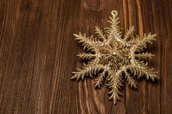 Golden snowflake on a wood Stock Photography