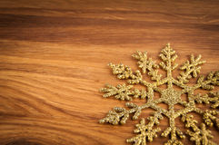 Golden  snowflake on wood. Stock Image