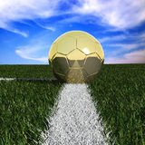 Golden soccer ball in the grass. Against the sky Stock Photos