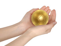 Golden soccer ball in hand Royalty Free Stock Photos