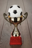 Golden soccer trophy cup. Golden football soccer trophy cup on the wooden table stock photography